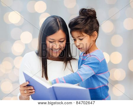 family, children, education, school and happy people concept - happy mother and daughter reading book over holidays lights background