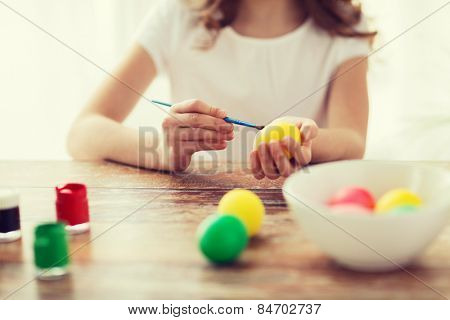 easter, holiday and child concept - close up of girl coloring eggs for easter
