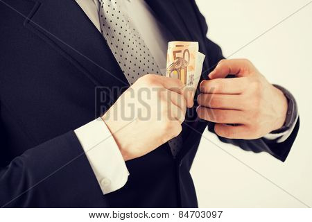 man hand putting euro cash money into suit pocket