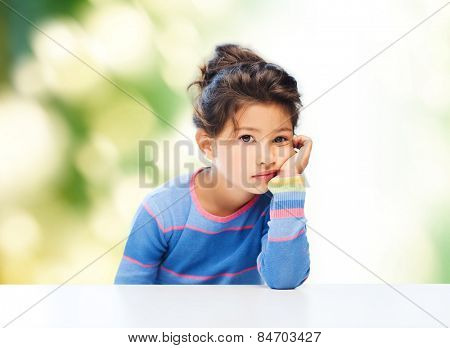 people, childhood and emotions concept - sad little girl over green background