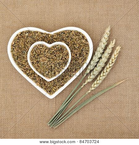 Green wheat feekeh in heart shaped bowls with fresh ears over hessian background.