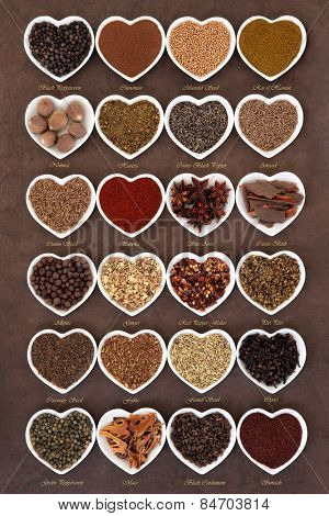 Large spice selection in heart shaped dishes over lokta paper background with titles.