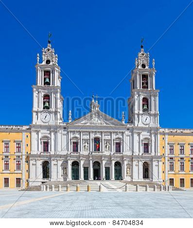 Mafra, Portugal - September 02, 2014: Tourists stroll in front of the Mafra National Palace, Convent and Basilica. Franciscan Religious Order. Baroque architecture.