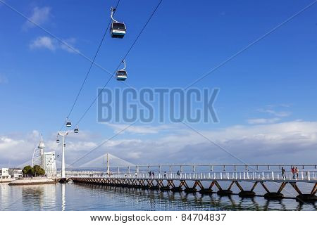 Lisbon, Portugal - February 01, 2015: People practicing sports on the Passeio Ribeirinho over the Tagus River. Vasco da Gama Tower and Bridge, Myriad Hotel and aerial tramway. Park of Nations