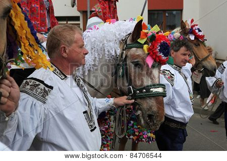 VLCNOV, CZECH REPUBLIC - MAY 26, 2013: Elderly men dressed in traditional Moravian folk costume lead decorated horses during the Ride of the Kings festival in Vlcnov, South Moravia, Czech Republic.
