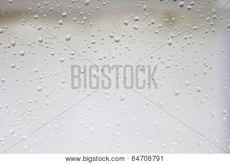 Wet glass with drops of rain fall on the street
