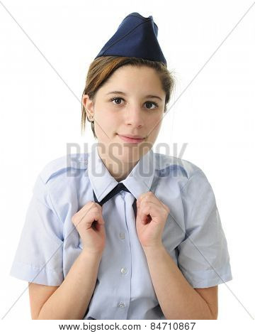 Closeup of a pretty teen girl straightening the tie of her C uniform.  On a white background.