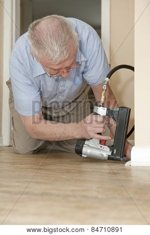 A senior man on his hands and knees, using an air-compressed stapler to attach new quarter round to his baseboards.  Space on bottom (home floor) for your text.