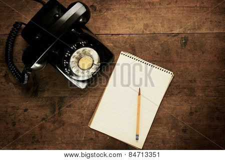 Note pad or memo pad and an old dial telephone on an grungy wooden board or surface. For inserting your custom message or text. Intentionally shot with low key shadows.
