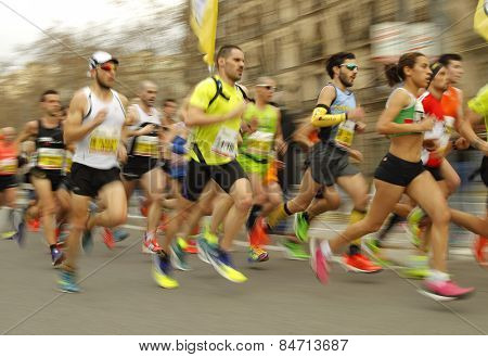 BARCELONA - FEB, 15: Group of runners in Barcelona streets running during Barcelona Half Marathon in Barcelona on February 15, 2015 in Barcelona, Spain.