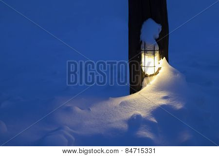 Outdoor lamp covered in snow.