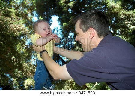 Dad Lifting Up Happy Baby