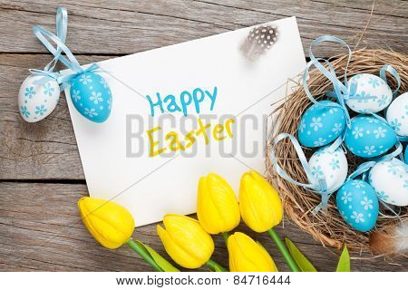 Easter greeting card with blue and white eggs and yellow tulips over wood. Top view with copy space