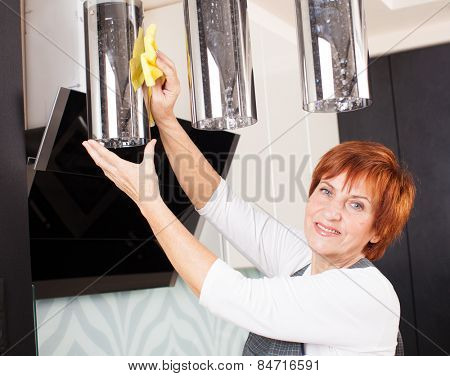 Woman cleaning the kitchen. Adult woman washing lamp