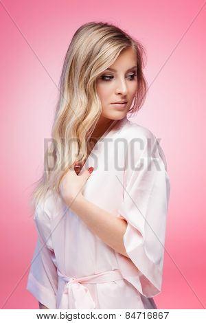 Young smiling blond lady wearing a sexy bathrobe on pink background