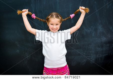 cute little girl in a white shirt against the school board raised pigtails