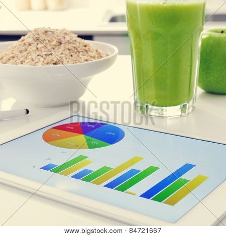 a tablet computer showing some charts and a bowl with cereals, a glass with a green smoothie and an apple on the kitchen table