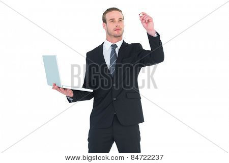 Serious businessman writing with marker and holding laptop on white background