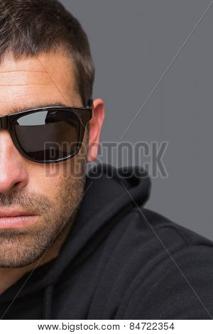 Criminal with sunglasses looking at camera in a shadowy setting