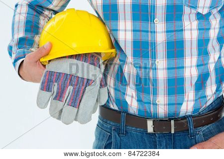 Close-up of construction worker holding hard hat and gloves on white background