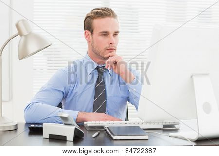 Businessman thinking with hand on chin at his desk in his office
