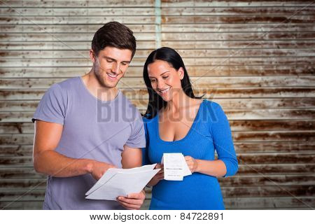 Young couple reading their bills against wooden planks