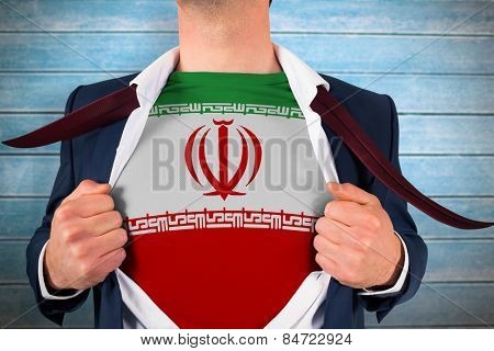 Businessman opening shirt to reveal iran flag against wooden planks