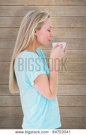 Pretty blonde standing and holding hot beverage against wooden planks