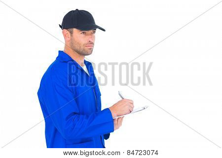 Male mechanic in blue overalls writing on clipboard over white background