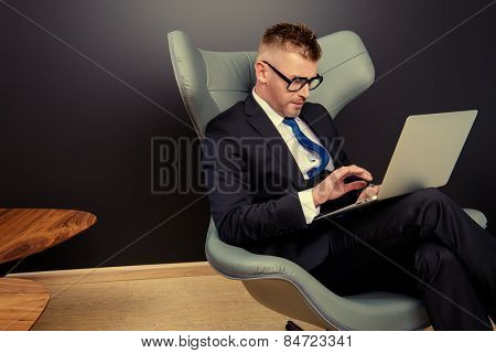 Imposing mature man in elegant suit sitting on a leather chair in a modern luxurious interior and working on a laptop. Fashion. Business.