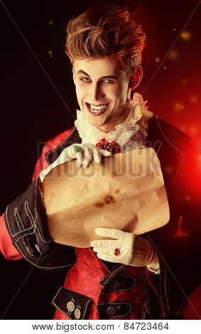 Attractive and frightening vampire holding a Sheepskin Scroll. Halloween. Dracula costume.