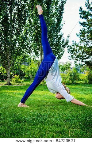 Beautiful young woman doing yoga, stretching exercise in the summer park. Healthy lifestyle. Yoga.