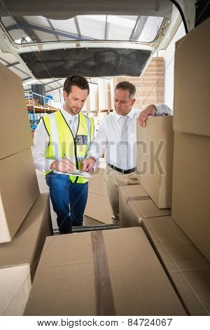 Delivery driver checking his list on clipboard in a large warehouse