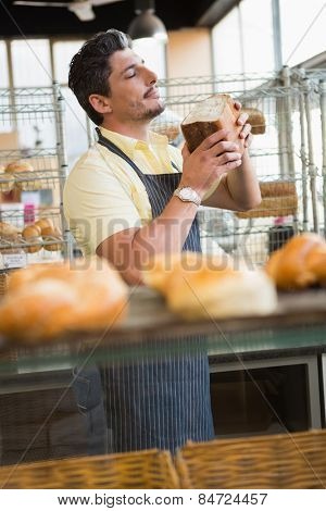 Smiling waiter smelling bread freshly baked at the bakery
