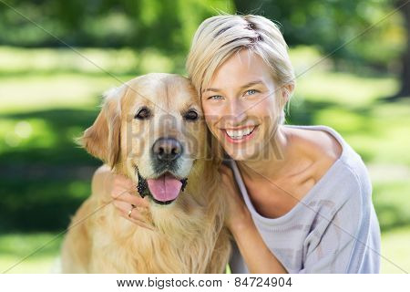 Pretty blonde with her dog in the park on a sunny day