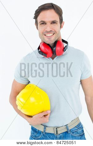 Portrait of happy carpenter with hard hat and ear protectors over white background