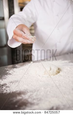 Close up of dough with flour on worktop in the kitchen of the bakery