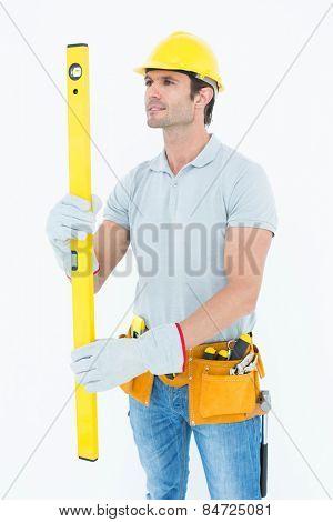 Handsome carpenter using spirit level over white background