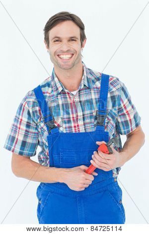 Portrait of confident plumber holding monkey wrench over white background