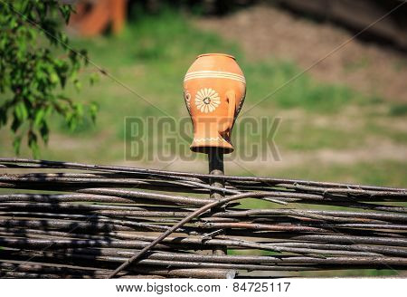 Traditional Ukrainian clay pot on wooden fence