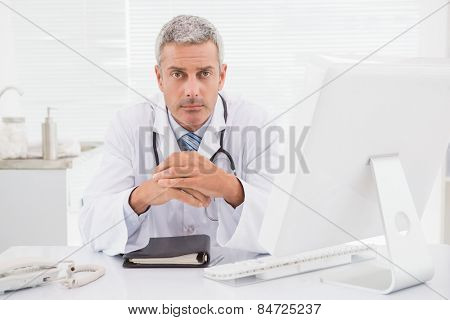 Unsmiling doctor looking at camera in medical office