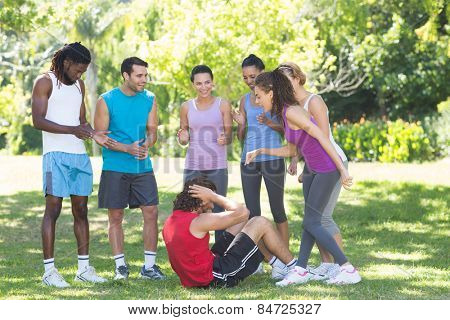 Fitness group encouraging man doing sit ups on a sunny day