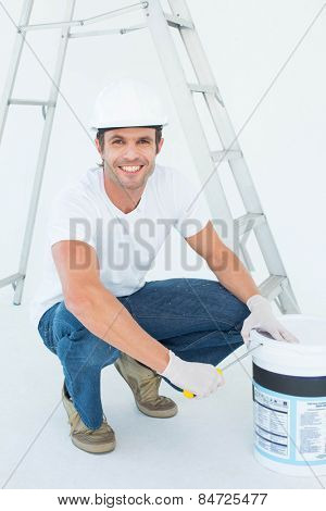 Full length portrait of happy man crouching while opening paint pot over white background