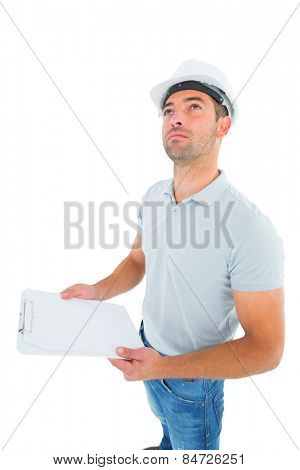 Manual worker looking up while holding clipboard on white background