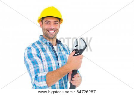 Portrait of smiling handyman holding adjustable spanner on white background