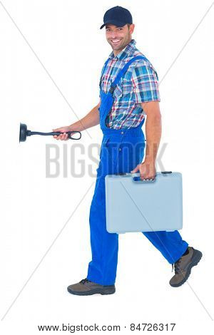 Full length portrait of happy plumber with plunger and toolbox walking on white background