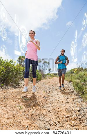 Fit attractive couple jogging down mountain trail against fitness interface