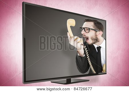 Geeky businessman shouting at telephone against pink vignette