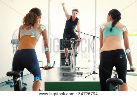 Fit women doing a spin class with enthusiatic instructor against fitness interface