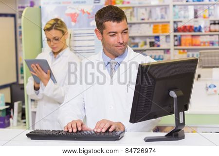 Smiling pharmacist using computer at the hospital pharmacy